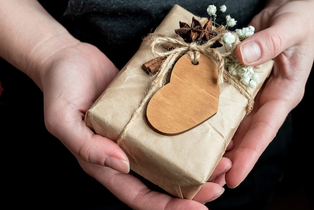 Kobieta trzyma w rękach słodkie pudełko zawinięte w papier rzemieślniczy ozdobiony drewnianym sercem i białymi kwiatami