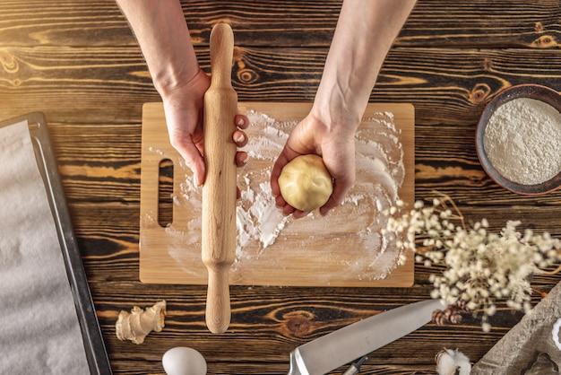 Kobieta trzyma w rękach surowe ciasto i wałek do ciasta do robienia pysznych domowych ciasteczek imbirowych w swojej kuchni