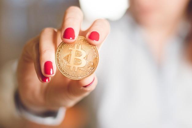 Kobieta trzyma w rękach złotą monetę