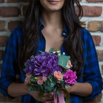 Kobieta trzyma w ręku bukiet fioletowej kombinacji kwiatów