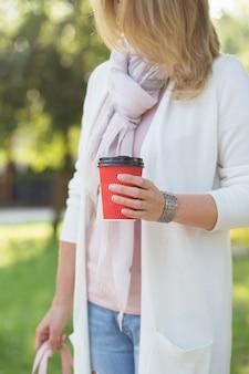 Kobieta trzyma w ręku czerwoną filiżankę kawy