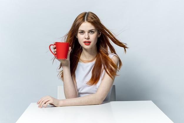 Kobieta trzyma w ręku czerwony kubek, siedząc przy stole