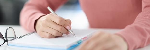 Kobieta trzyma w ręku długopis i robi notatki w pamiętniku. planowanie i ustalanie koncepcji codziennych zadań
