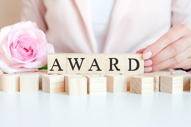 Kobieta trzyma w ręku drewnianą kostkę z tekstem nagrody