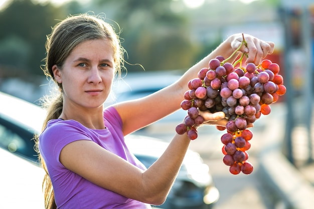 Kobieta trzyma w ręku dużą grupę czerwonych soczystych winogron.