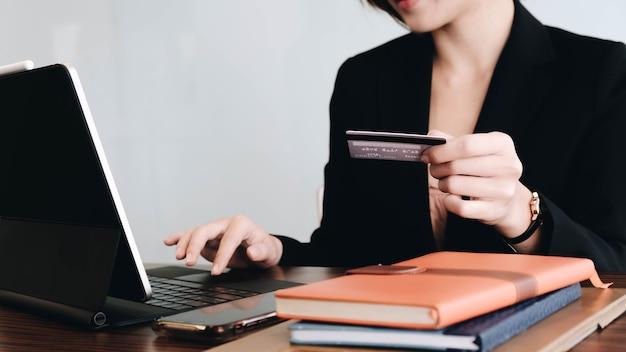 Kobieta trzyma w ręku kartę kredytową i używa laptopa do robienia zakupów w internecie na drewnianym stole.