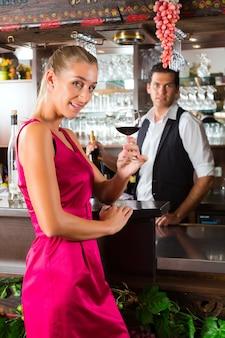 Kobieta trzyma w ręku kieliszek wina w barze