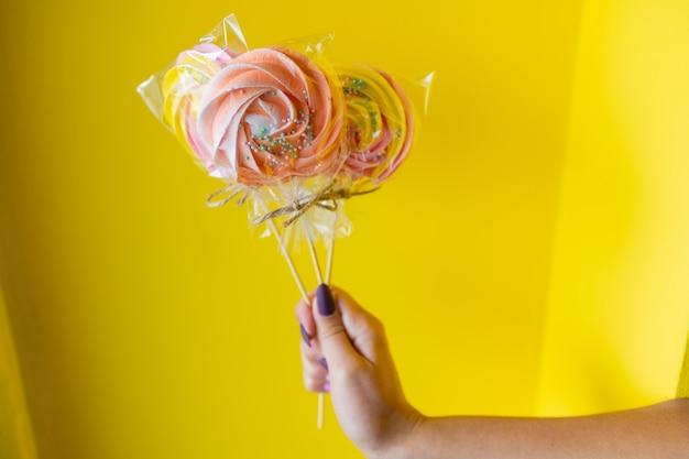 Kobieta trzyma w ręku kolorowy cukierek.
