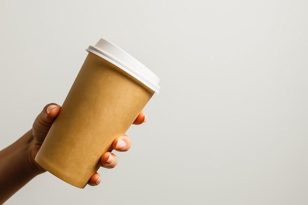 Kobieta trzyma w ręku papierowy kubek z kawą lub herbatą. pij czas na kawę. jednorazowy kubek papierowy. piękne blond włosy młoda dziewczyna. styl casual, biała koszula i jeansy. na wynos. gorący napój. pusta przestrzeń
