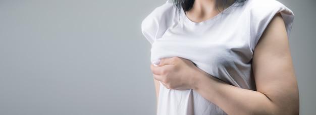 Kobieta trzyma w ręku pierś. koncepcja bólu w klatce piersiowej