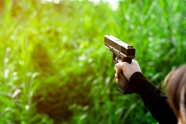 Kobieta trzyma w ręku pistolet. - pojęcie przemocy i przestępczości.