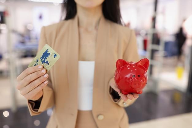 Kobieta trzyma w ręku plastikową kartę kredytową i czerwoną świnię skarbonkę
