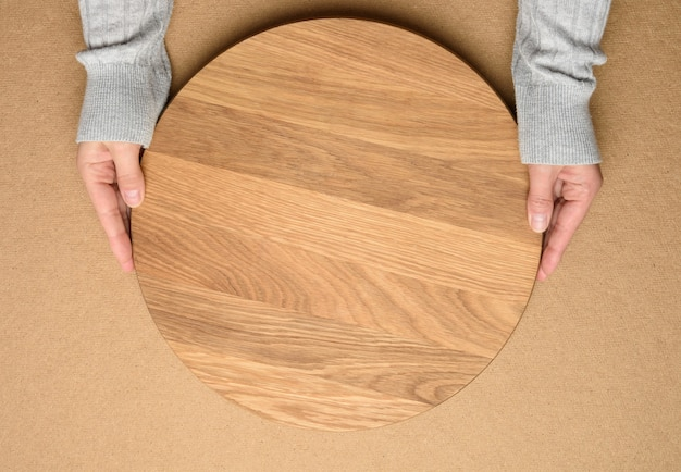 Kobieta trzyma w ręku pustą okrągłą drewnianą deskę do pizzy, ciało na brązowym tle, widok z góry
