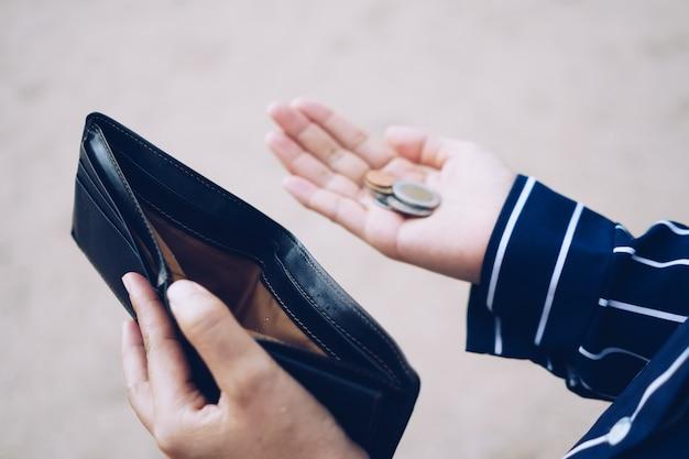 Kobieta trzyma w ręku pustą torebkę i monety, co oznacza problem finansowy z pieniędzmi lub zbankrutował bezrobotny, zepsuł się po wypłacie karty kredytowej bez pracy, pojęcie zadłużenia.