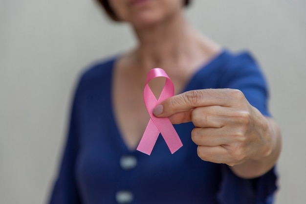 Kobieta trzyma w ręku różową kokardkę. kampania profilaktyki raka piersi. różowy październik