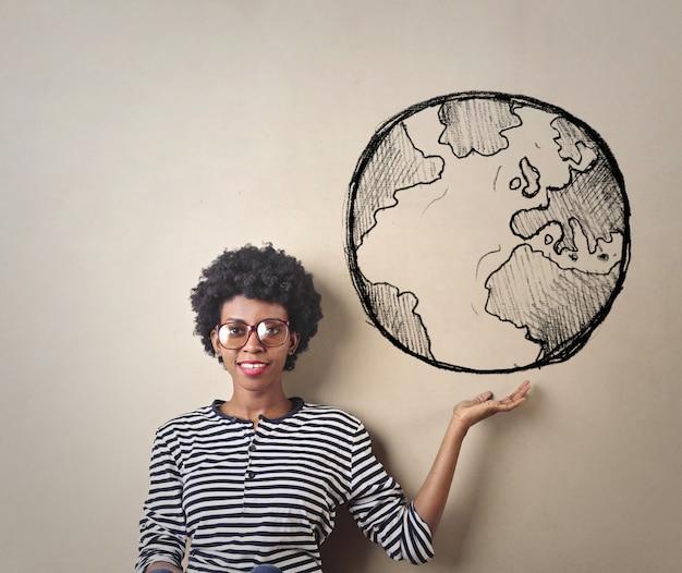 Kobieta trzyma w ręku rysunek świata