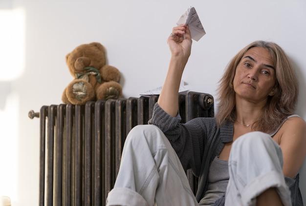 Kobieta trzyma w ręku samolot wykonany z kartki papieru z nutami, który siedzi na podłodze w jej mieszkaniu