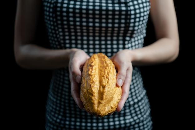 Kobieta trzyma w ręku strąki surowego kakao. świeże kakao na plantacji.