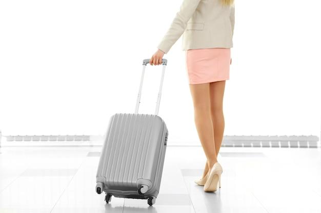 Kobieta trzyma walizkę na lotnisku