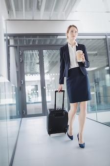 Kobieta trzyma walizkę spacerując po biurze