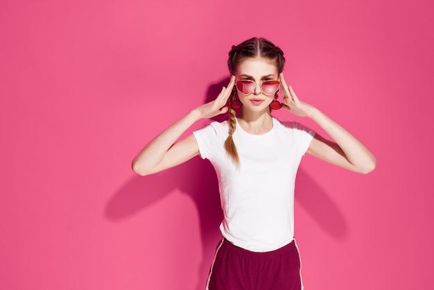 Kobieta trzyma warkocze w okularach przeciwsłonecznych letnie ubrania moda glamour