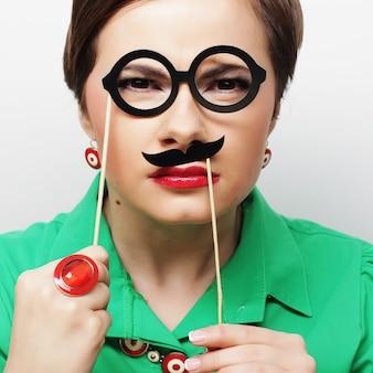 Kobieta trzyma wąsy i okulary na patyku.