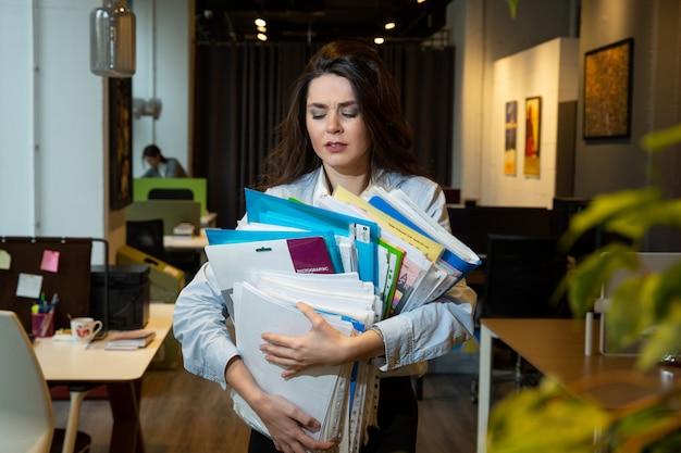 Kobieta trzyma wiele folderów