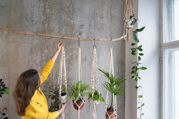 Kobieta trzyma wieszak na rośliny makramy z roślin doniczkowych na szarej ścianie