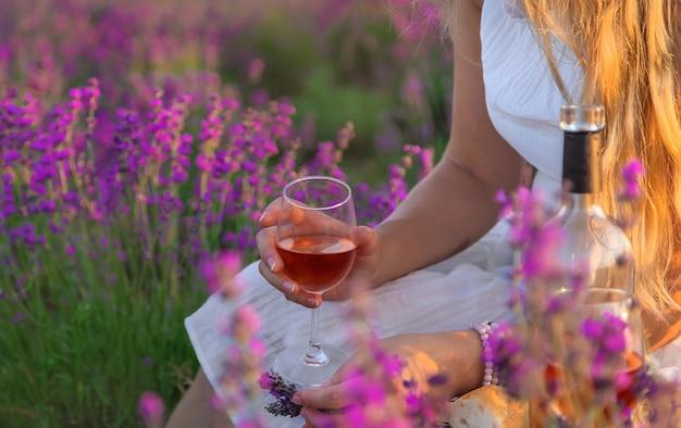 Kobieta trzyma wino w kieliszkach. piknik w lawendowym polu. selektywne skupienie.