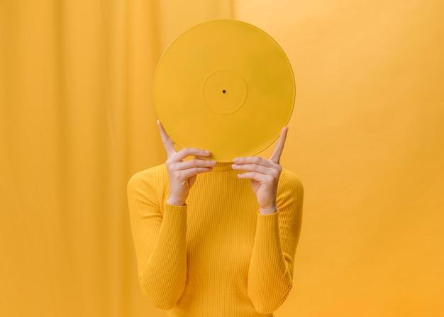 Kobieta trzyma winylu przed twarzą w żółtej scenie
