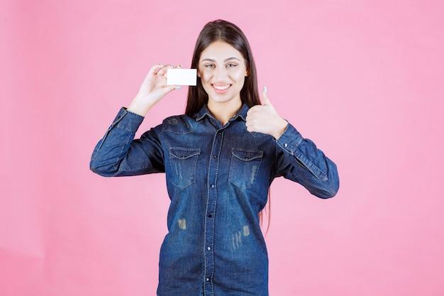 Kobieta trzyma wizytówkę i pokazuje radość ręką znak