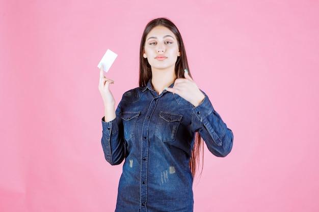 Kobieta trzyma wizytówkę i prosi o telefon