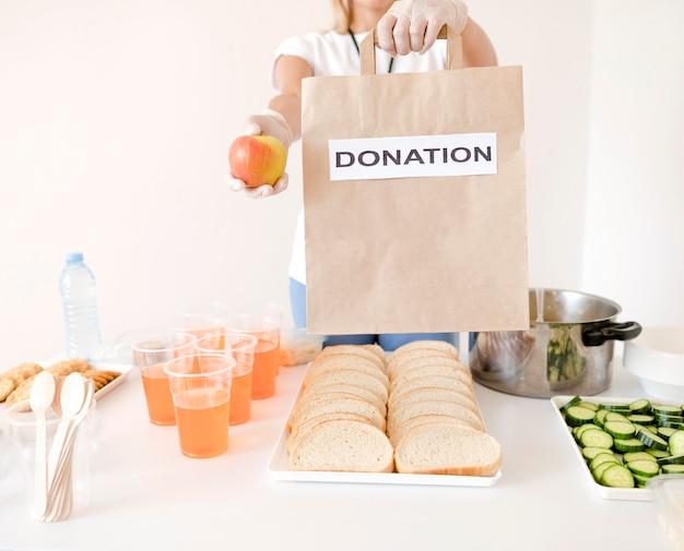 Kobieta trzyma worek darowizny z jedzeniem