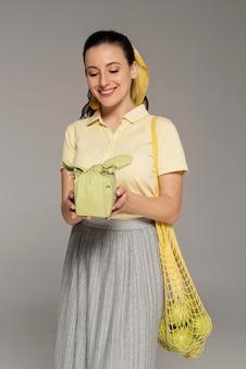 Kobieta trzyma worek serwetki i żółwia wielokrotnego użytku