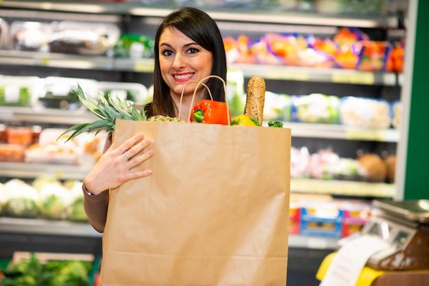 Kobieta trzyma worek zdrowej żywności w sklepie spożywczym