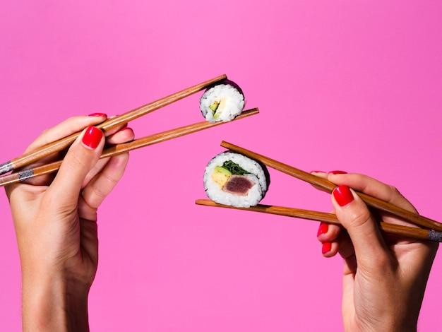 Kobieta trzyma z obu dłoni sushi rolki na pałeczki