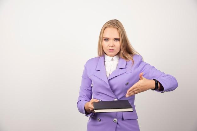 Kobieta trzyma zamknięty schowek na biały.