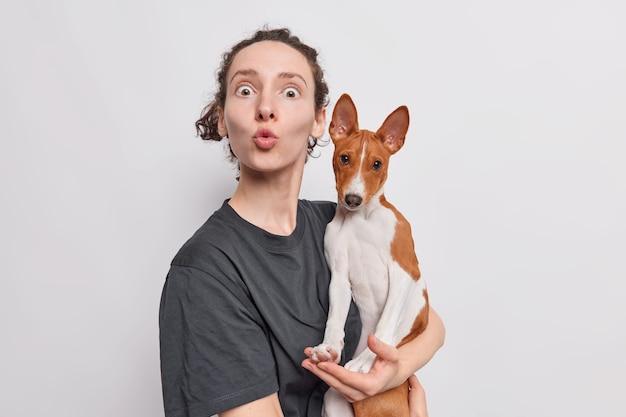 Kobieta trzyma zaokrąglone usta, wpatruje się w szoku, trzyma pies basenji, robi sobie zdjęcie, a zwierzak robi zabawny grymas na białym tle