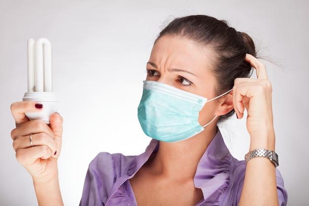 Kobieta trzyma żarówkę podczas gdy będący ubranym maskę