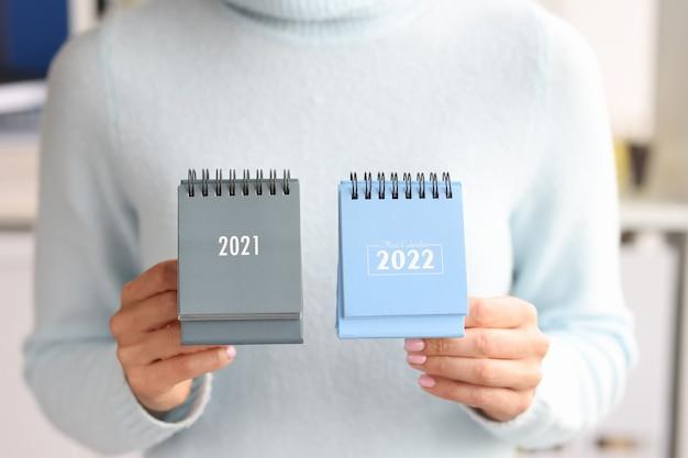 Kobieta trzyma zbliżenie kalendarz 2021 i 2022. zmiana roku kalendarzowego
