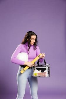 Kobieta trzyma zestaw do makijażu i zestaw budowlany