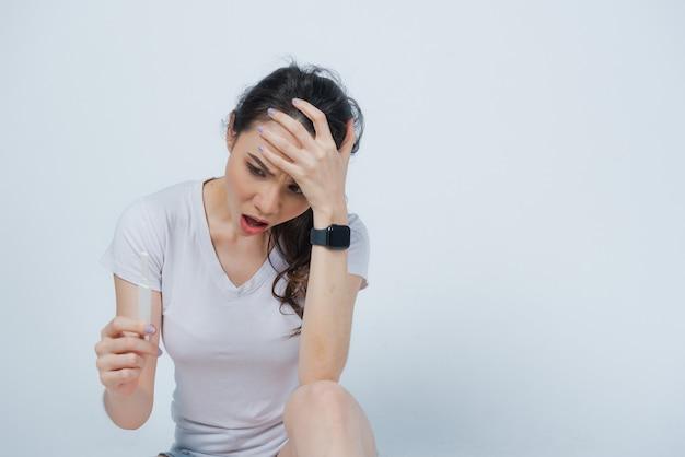 Kobieta trzyma zestaw do testu ciążowego, kobiety w ciąży