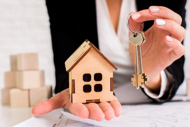 Kobieta trzyma zestaw kluczy z drewnianym domu