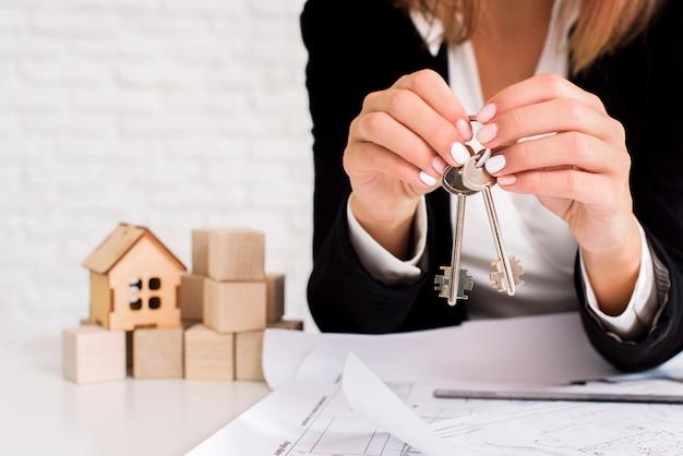 Kobieta trzyma zestaw kluczy z drewnianymi sześcianami