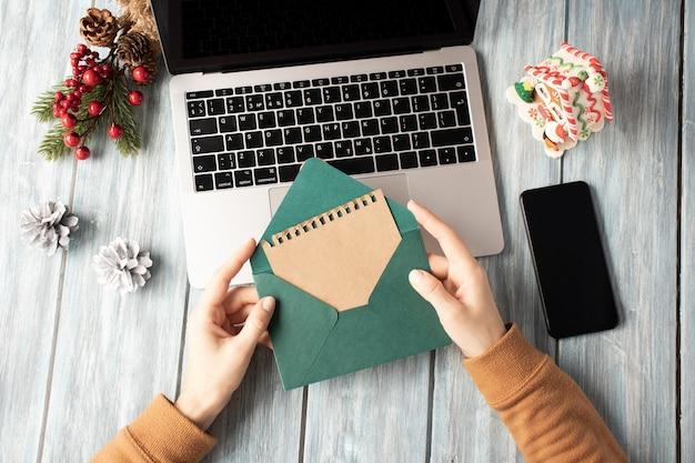 Kobieta trzyma zieloną kopertę na laptopie z atmosferą bożego narodzenia w biurze