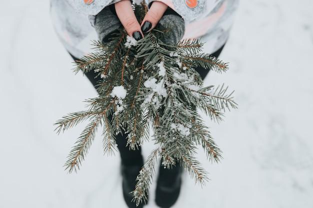 Kobieta trzyma zielone gałęzie sosny ze śniegiem na niewyraźne tło