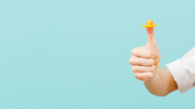Kobieta trzyma żółtego kondom na jej palcu z kopii przestrzenią