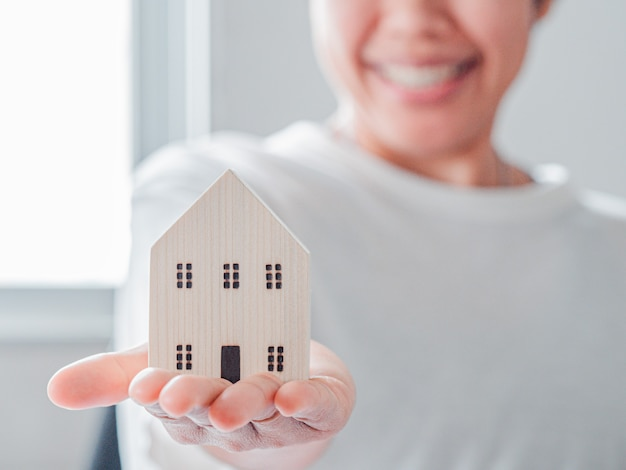 Kobieta trzymać model domu i uśmiech twarz kobiety w tle