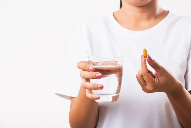 Kobieta trzymać olej z ryb witaminy leki w ręku gotowe wziąć leki ze szklanką wody