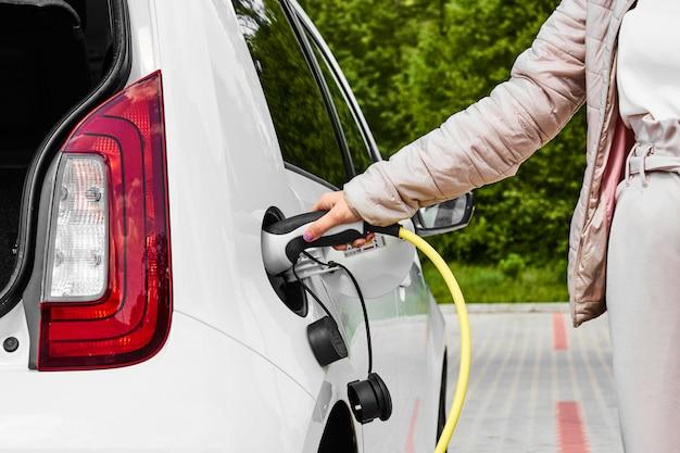 Kobieta trzymać zasilacz podłączony do samochodu elektrycznego w publicznej stacji ładującej na zewnątrz.
